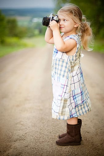 Girl in white blue plaid dress shirt and black boots standing on road during daytime