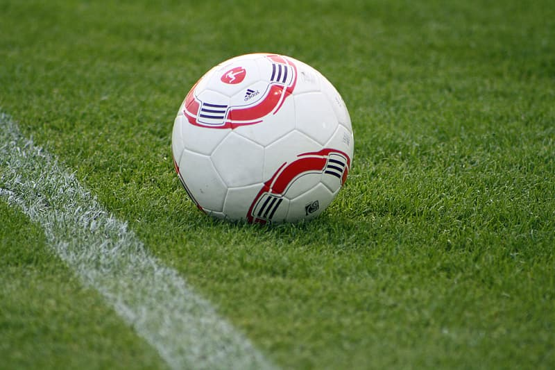 White and red soccer ball on green grass field during daytime