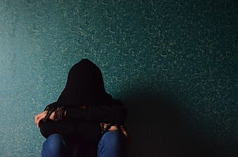Person in black hooded apparel and blue denim jeans sitting hiding his face between hands photo