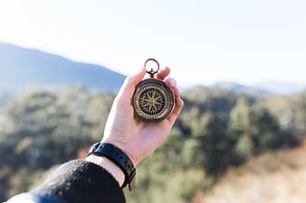 Person showing brown compass