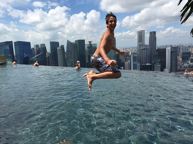 Boy jumping on to infinity pool