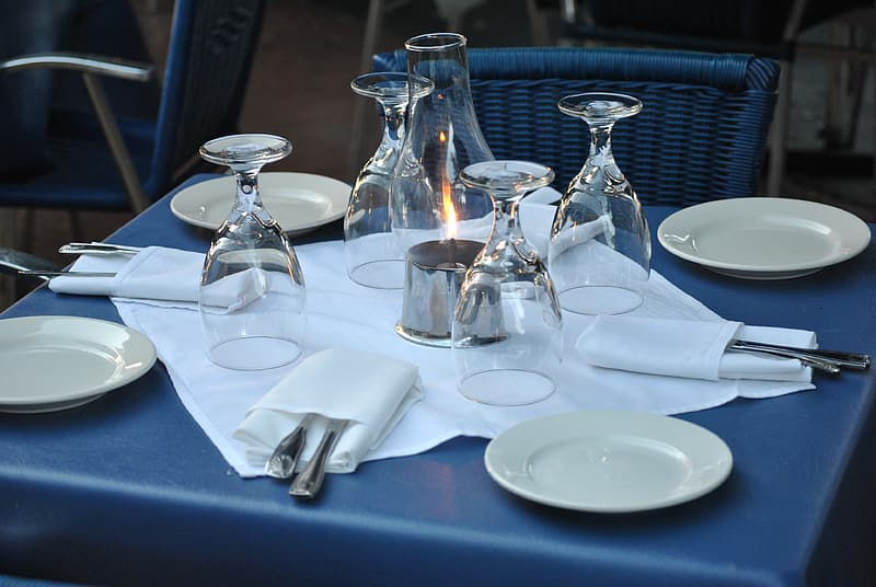 White ceramic plate with wine glass on blue square top table