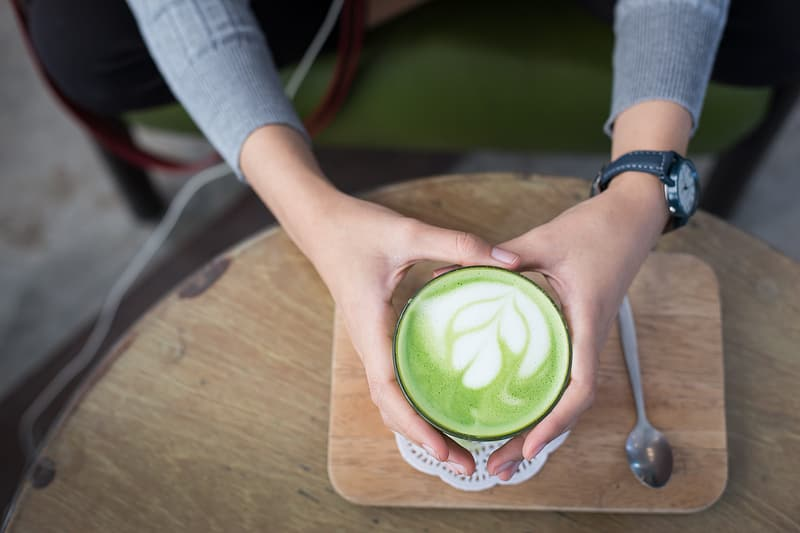 Person holding ceramic cup with capuccino