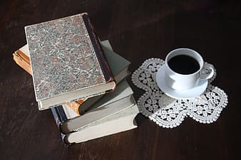 Filled white cup on top of white saucer near four piled books