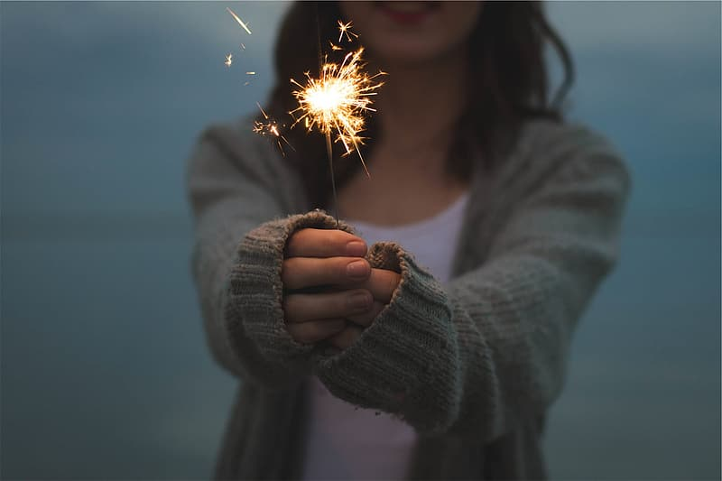 Woman in gray sweater holding sparkler