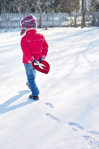 Boy wearing blue jeans and walking in sno