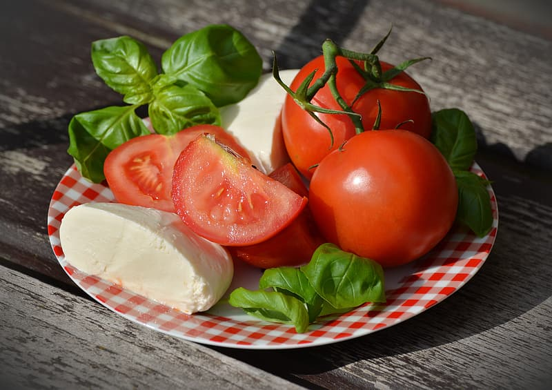 Sliced tomatoes, basil, and parmesan cheese served on plate