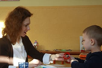 Woman wearing brown cardigan sitting facing on boy wearing black long-sleeved shirt