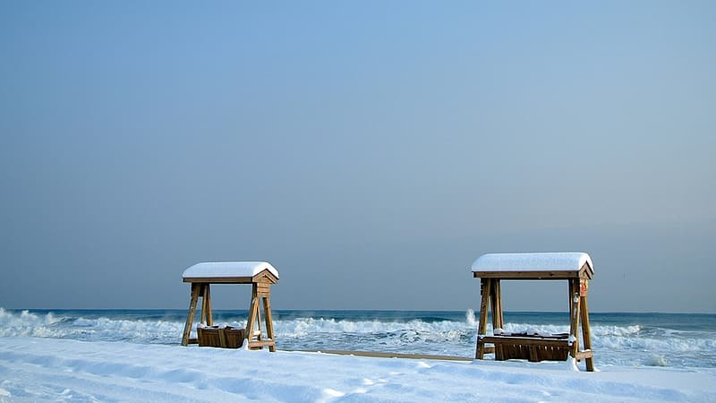 Brown wooden beach chair on white snow covered ground during daytime