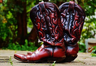 Pair of red-and-black leather cowboy boots on gray concrete pavement