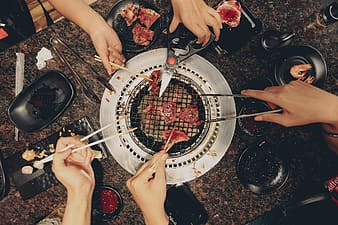 Group of five people grilling meat in tabletop grill
