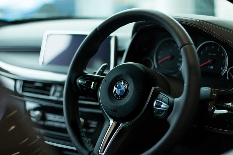 Shallow focus photography of black BMW steering wheel