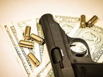 Black pistol, bullet shells, and US dollar banknotes on white surface