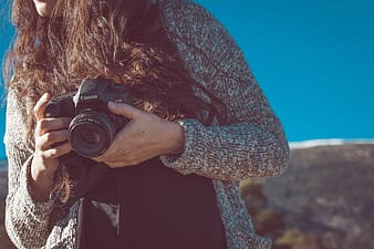 Woman wearing brown knit cardigan holding camera