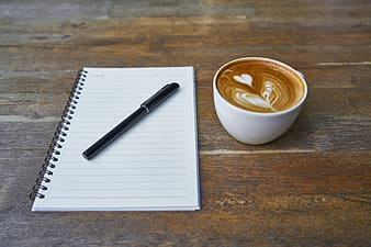Black pen on spiral notebook beside cappuccino art