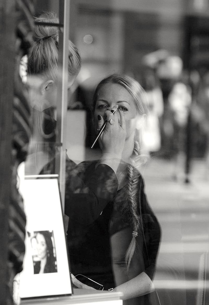 Grayscale photography of woman putting makeup on another woman