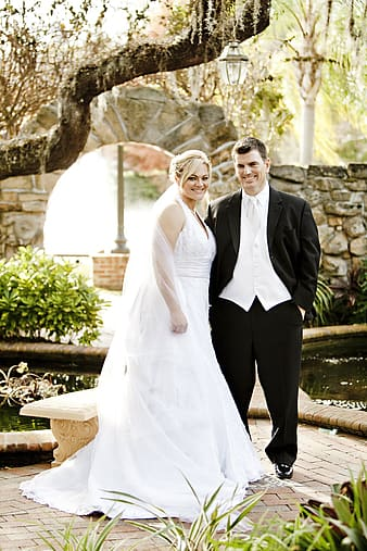 Woman wearing white wedding dress and man wearing wedding outfit smiling