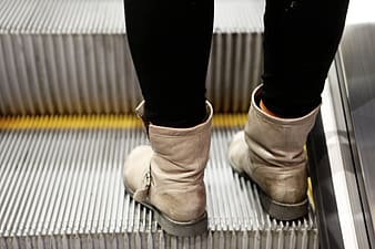 Person wearing pair of beige leather boots on escalator
