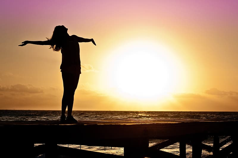Silhouette of woman spreading hand standing on port near body of water with sunset view
