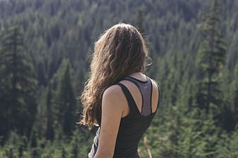 Woman in black and gray tank top standing distance forest during daytime