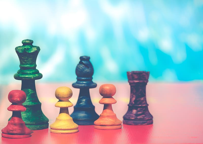 3 green chess pieces on brown wooden table
