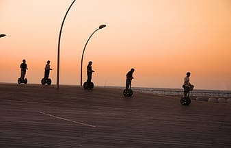 Five people riding personal transport machine