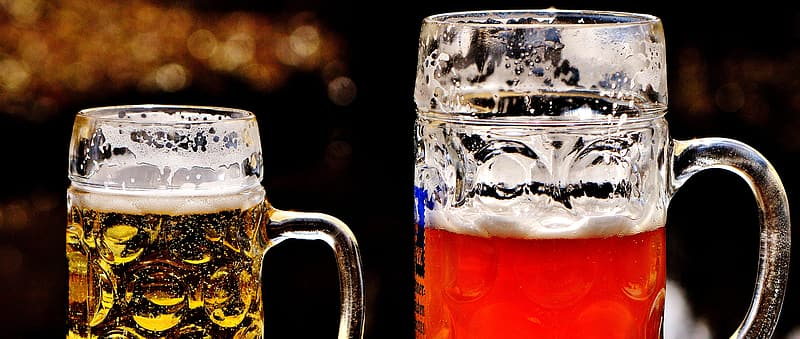 Two clear glass beer mugs filled with beverages