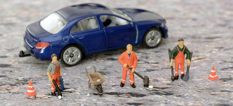 Closeup photography of blue sedan and three construction men workers figurines