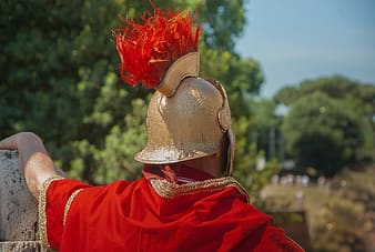 Man wearing beige helmet and red cape during daytime