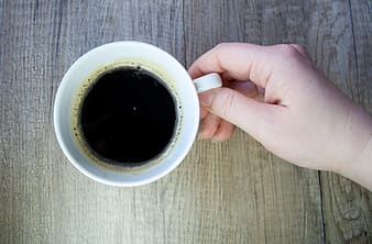 Person holding white ceramic mug filled with black coffee