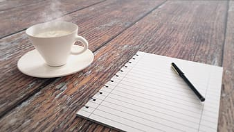 Black pen on white lined printer paper near white mug filled with coffee