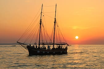 Black junk boat on body of water during sunset