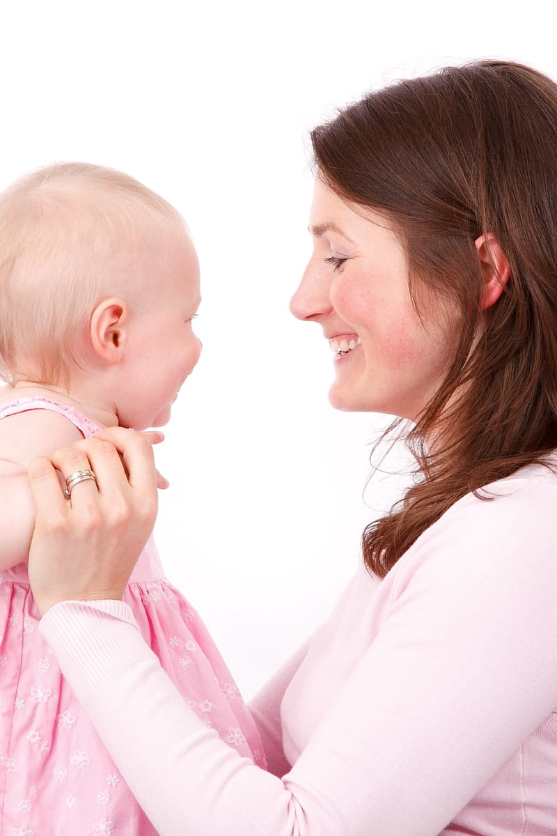 Photo of mother and child wearing pink sweatshirt and dress
