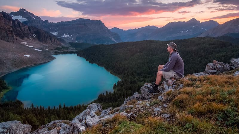 Man on sitting on rock cliff photography
