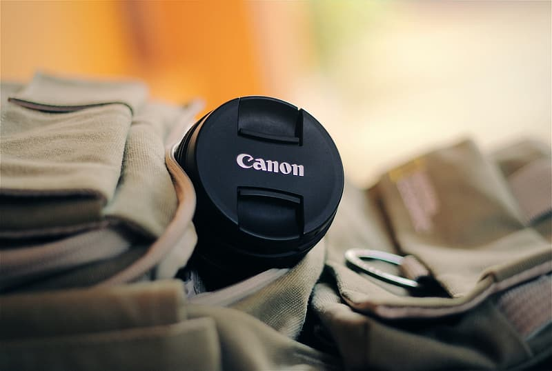Selective focus of black Canon telephoto lens on brown bag