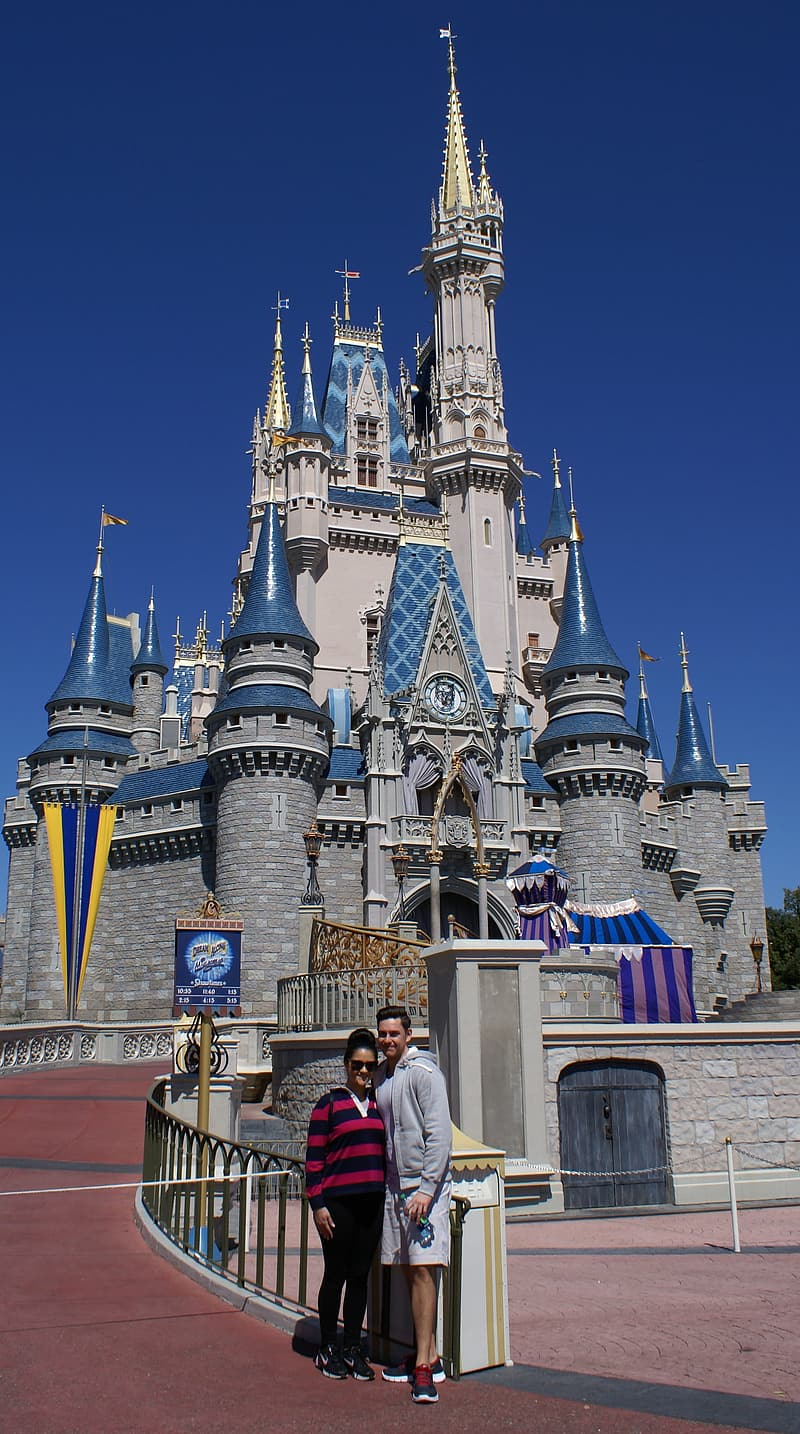Man and woman taking picture infront of Walt Disney castle