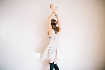 Woman in white dress covering face with her hands