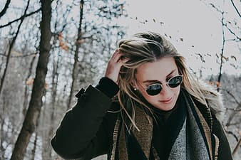 Woman in black coat and black aviator-style sunglasses