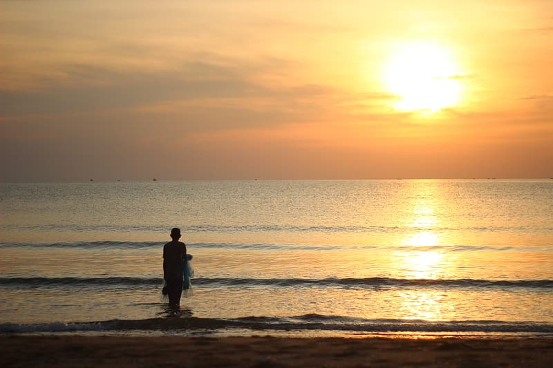 Silhouette of man standing on beach during sunset