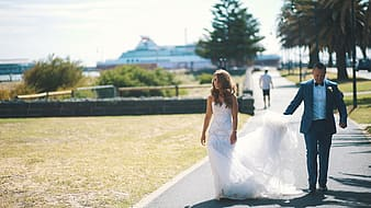Woman in white gown walking along with man in black