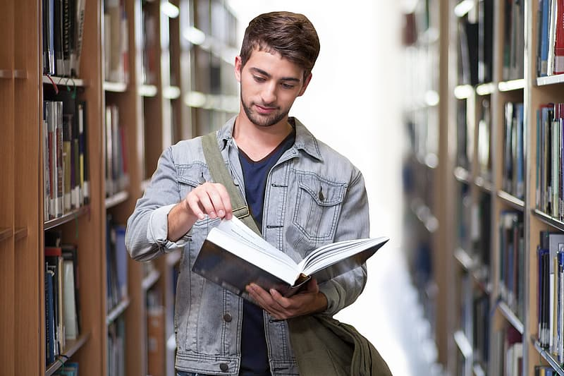 Man holding a book inside library