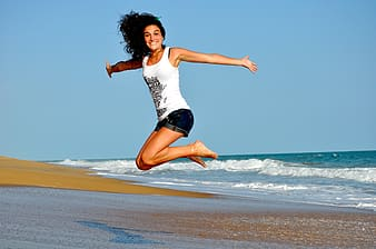 Women's white and black floral dress, woman wearing white tank top jumping near seashore