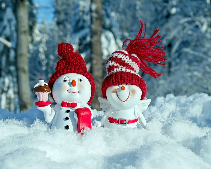 Two white-and-red snowman figurines standing on snow field