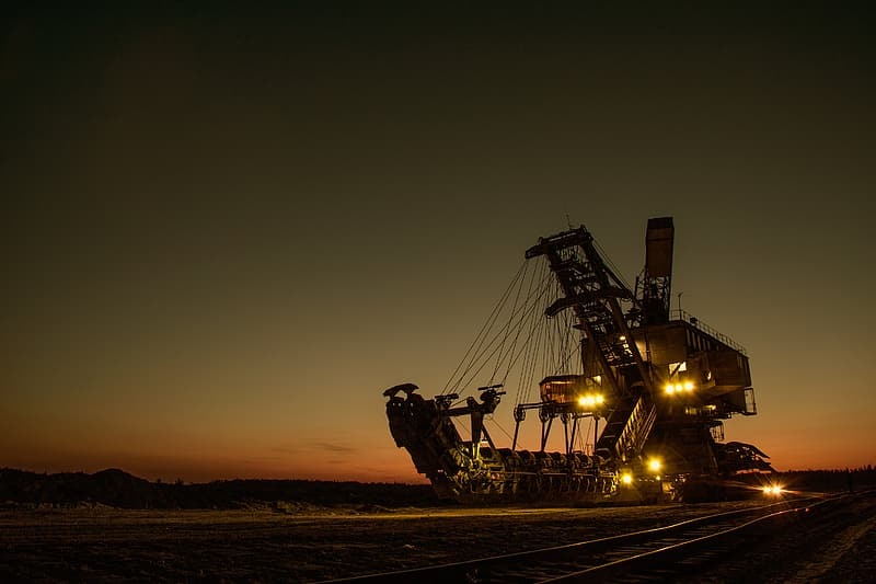 Brown heavy machinery with lights during golden hour
