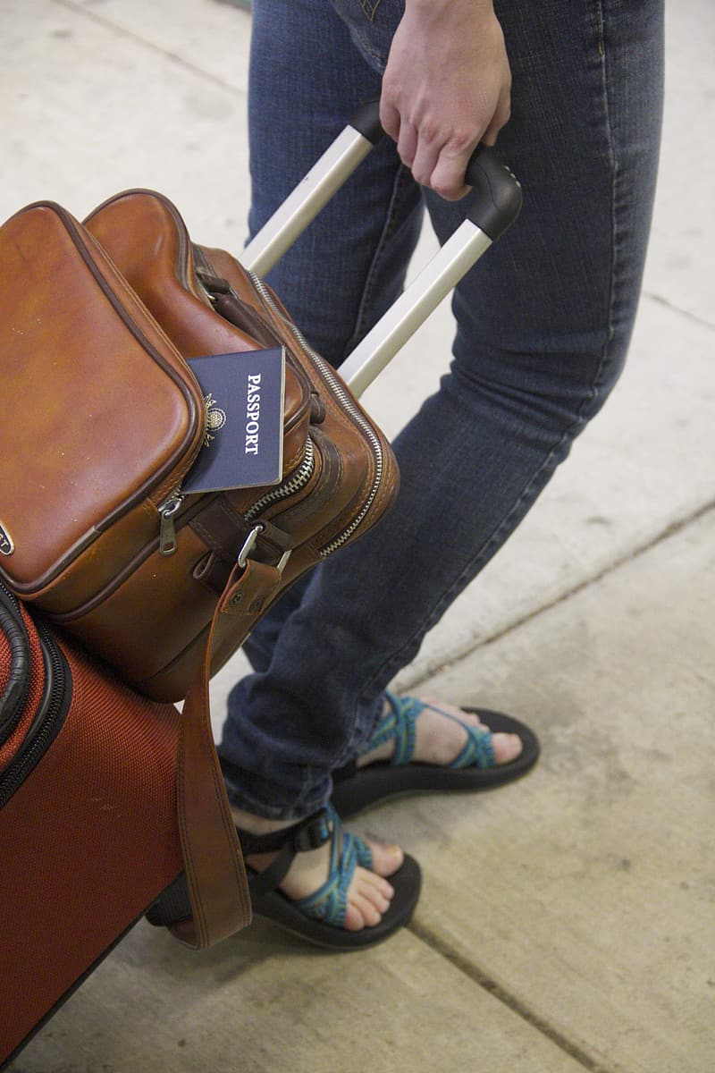 Person in blue denim jeans and brown leather bag