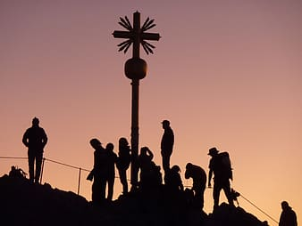 Silhouette of brown wooden cross and people