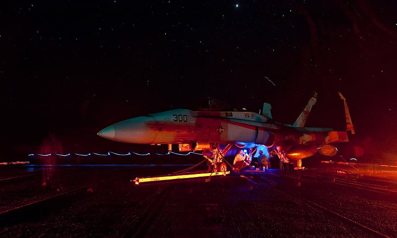 White and red jet plane on the road during night time