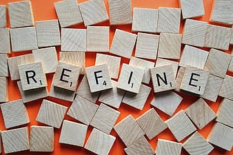 Scrabble tiles forming the word refine on orange surface