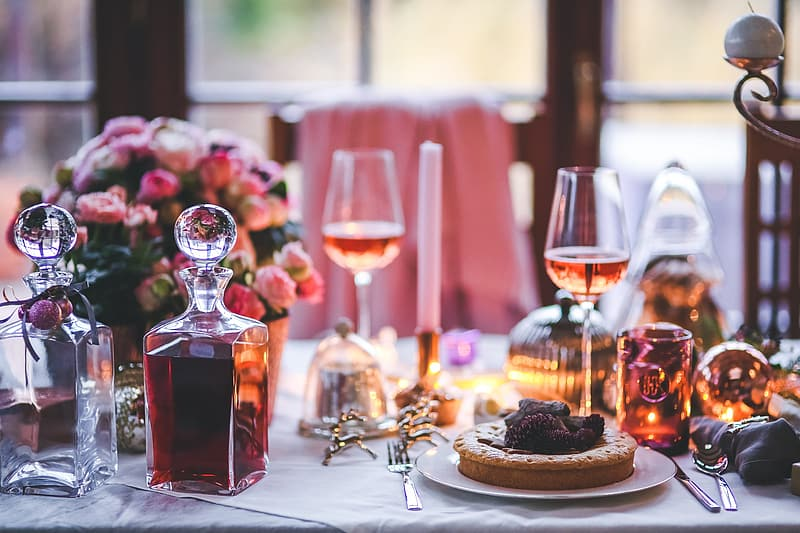 Two glass decanter filled with wine on table with plate of pies and wine glasses