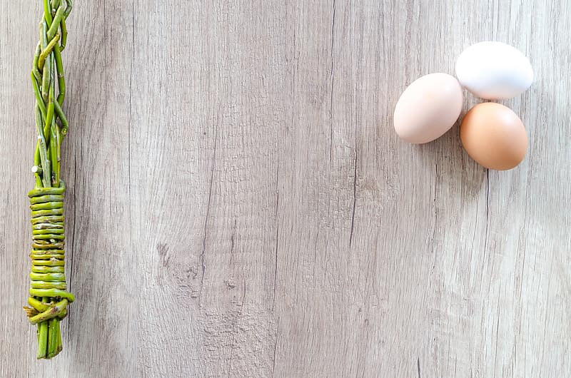 Three eggs on brown wooden board